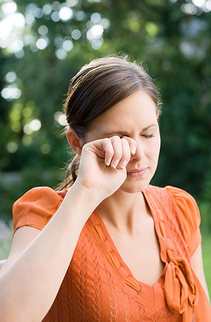 woman with allergies rubbing her eye